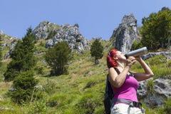 Trekker женщины выпивая пока отдыхающ высоко в горах стоковые изображения
