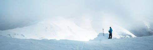 Trekker зимы оставаясь на горном пике он взобрался и enjojing широкий взгляд panorame долины покрытый облаками шторма актеров стоковые изображения