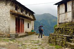 Trekker with backpack in a mountain village Royalty Free Stock Photos