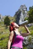 Trekker de femme buvant tout en se reposant haut dans les montagnes Photos stock