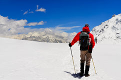 Trekker de la montaña que mira las altas montañas de Himalaya del invierno Imagen de archivo libre de regalías