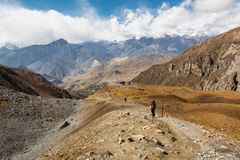 Trekker descending mountain on dirt path surrounded by wasteland. Royalty Free Stock Image