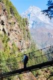Trekker die kabelbrug op trekkingsroute kruisen Royalty-vrije Stock Foto's