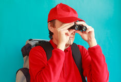 A trekker during an excursion looking through his binoculars. A trekker is a hike in the mountains with his backpack and his binoculars observes the landscape Stock Photos