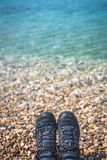 Trekker feet on the stony beach. Close up of a man legs wearing black shoes resting on a stony beach in summer Royalty Free Stock Photos