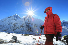 Trekker and flare over nuptse summit beside of everest Stock Photos