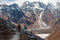Trekker goes down fron Larke La pass on Manaslu circuit trek in. Nepal stock image