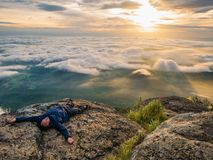 Trekker Lay down on the cliff with Beautiful Sunrise and sea of mist in the morning on Khao Luang mountain. In Ramkhamhaeng National Park,Sukhothai province stock image