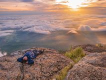 Trekker Lay down on the cliff with Beautiful Sunrise and sea of mist in the morning on Khao Luang mountain. In Ramkhamhaeng National Park,Sukhothai province royalty free stock photography