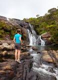 Trekker looks at wild waterfall Stock Photo