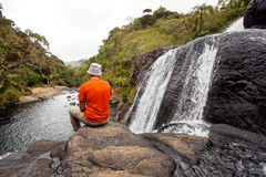 Trekker looks at wild waterfall Royalty Free Stock Images