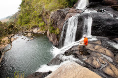 Trekker looks at wild waterfall in Horton Plains National Park, Royalty Free Stock Image