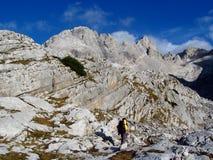 Trekker met een rugzak die in rotsachtige bergen wandelen stock afbeeldingen