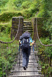 Trekker passing on a suspension bridge Royalty Free Stock Image