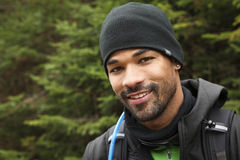 Trekker's portrait. Portrait of a black man with trekking clothes and equipment taken outdoors during a cold and cloudy autumn day Stock Image
