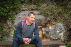 Trekker sitting on a bench. Caucasian male with a backpack pausing to rest on a bench while walking on a path in a forest on a coastal trail in Petrovac royalty free stock photo