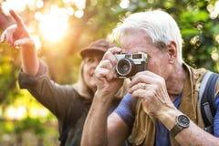 Trekker supérieur prenant une photo avec un appareil-photo de film Photographie stock