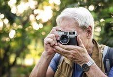 Trekker supérieur prenant une photo avec un appareil-photo de film Photographie stock libre de droits