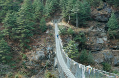 Trekker on suspension bridge Royalty Free Stock Photos
