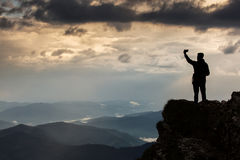 Trekker taking selfie on a mountain with beautiful storm clouds stock photo