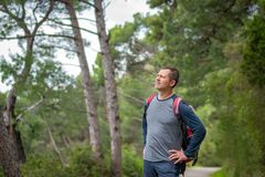 Trekker on a trail. Caucasian male with a backpack pausing to look at a landscape while walking on a path in a forest on a coastal trail in Petrovac, Montenegro stock photography