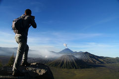 Trekker And Volcano. Trekker taking photo of Gunung Bromo volcano in Java, Indonesia royalty free stock images