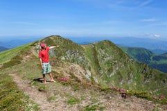 Trekker walking flowers field in mountain Stock Images