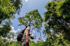 Trekker is walking among grassy trail Stock Photography