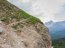 Trekker walking on path upon dolomitic rock wall, Tofana Mountain Group. Cortina d`Ampezzo, Italy royalty free stock image