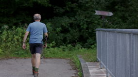 Trekker walks across the road bridge stock video