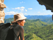 A trekker woman with a hat. Looking over the mountains and the jungle from the Great Wall of China - China Stock Photography
