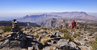 Trekkers on Approach Route to Jabal Shams. This is the approach route from the Pulpit. Jabal Al Kwar massive is clearly seen in the far distance Stock Image
