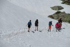 Trekkers che camminano su un aumento alle montagne della neve Fotografia Stock