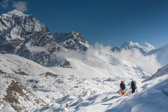 Trekkers crossing Gokyo glacier in Khumbu valley on a way to Eve. Rest Base camp stock photo