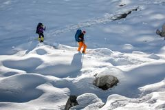 Trekkers are crossing Gokyo glacier in Khumbu valley on a way to. Everest Base camp Stock Photos