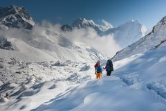 Trekkers crossing Gokyo glacier in Khumbu valley on a way to Eve. Rest Base camp royalty free stock images