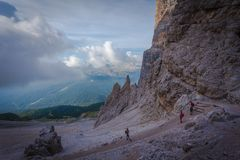 Trekkers descend along path in a cloudy day. Tofane area, Dolomites, Cortina d`Ampezzo, Italy stock image