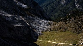 Trekkers dwarfed by mountain scenery, walking in the distance on stock images