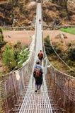 Trekkers en kabelbrug op trekkingsroute Stock Afbeeldingen