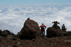 Trekkers gazing over the clouds Stock Image