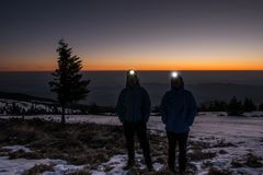 Trekkers with headlamps at winter sunrise in the mountains Royalty Free Stock Photos