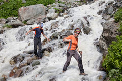 Trekkers kruist mountanious rivier Stock Foto's