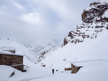 Trekkers marchant sur le passage de montagne de neige avec les loges le long de la route Photos libres de droits
