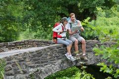 Trekkers relaxing on the stone bridge Royalty Free Stock Image