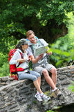 Trekkers taking break reading map in forest Royalty Free Stock Photos