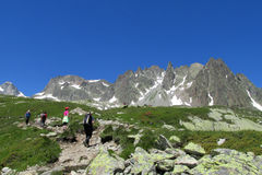 Trekkers walking on a hike to mountains Stock Image