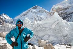 Trekkes is posing at camera in front of huge glacier falling fro. M Everest close to Everest base camp royalty free stock image