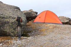Trekking ручки горы стоят около камня около оранжевого trekking шатра на дезертированных каменных наклонах elbrus Стоковая Фотография RF