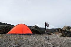 Trekking ручки горы стоят около камня около оранжевого trekking шатра на дезертированных каменных наклонах elbrus Стоковое Изображение