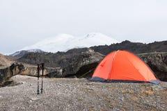 Trekking ручки горы стоят около камня около оранжевого trekking шатра на дезертированных каменных наклонах elbrus Стоковое фото RF